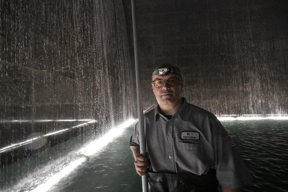"""James Maroon, an engineer at the 9/11 Memorial, poses near the waterfalls in the south pool, Wednesday, Aug. 4, 2021 in New York. On Sept. 11, 2001 he was going to work at the New York Mercantile Exchange, just west of the World Trade Center. He knew about 20 brokers at Cantor Fitzgerald that worked at the exchange. """"They had a meeting that morning in one of the towers,"""" he recalled. All their brokers, except for one, perished that day. Sometimes when we're outside I look at the panel that their names are on. And one of them Elkin Yuen, his daughter was due to be born. Now she's going to be 20 years old. And never met her father."""" (AP Photo/Mark Lennihan)"""