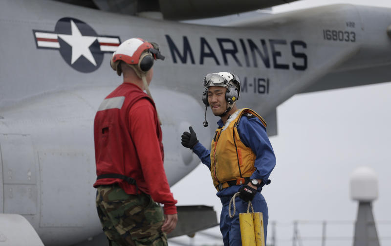 Japanese crewmember Yoshinuri Matsumura, right, gestures towards U.S. Navy Seaman Michael Petrich as they secure a Marine MV-22 Osprey aircraft after it landed on the Japanese destroyer JS Hyuga Friday, June 14, 2013, in coastal waters off San Diego. The aircraft made an unprecedented landing on the vessel Friday, despite protests in Japan over concerns over the tilt-rotor aircraft's safety record. (AP Photo/Gregory Bull)