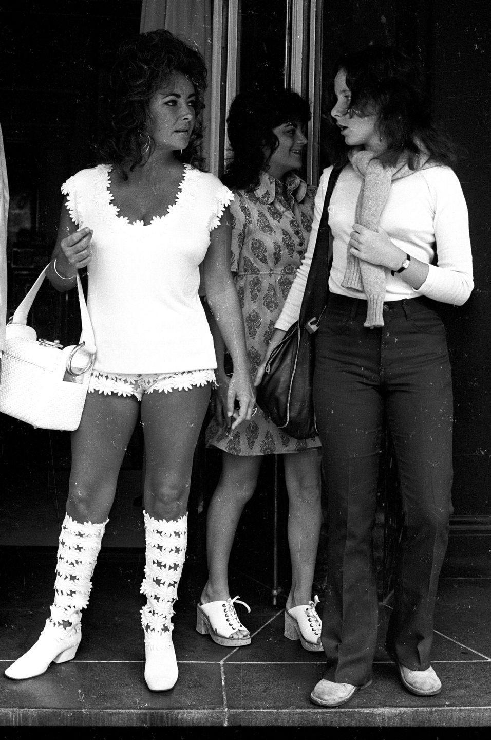 <p>Elizabeth dresses in floral boots and white hot pants for a day out with her eldest daughter, Elizabeth Liza Todd. </p>