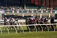 Pierre-Charles Boudot, left in purple silks, rides Order of Australia to win the Breeders' Cup Mile horse race at Keeneland Race Course, in Lexington, Ky., Saturday, Nov. 7, 2020. (AP Photo/Mark Humphrey)