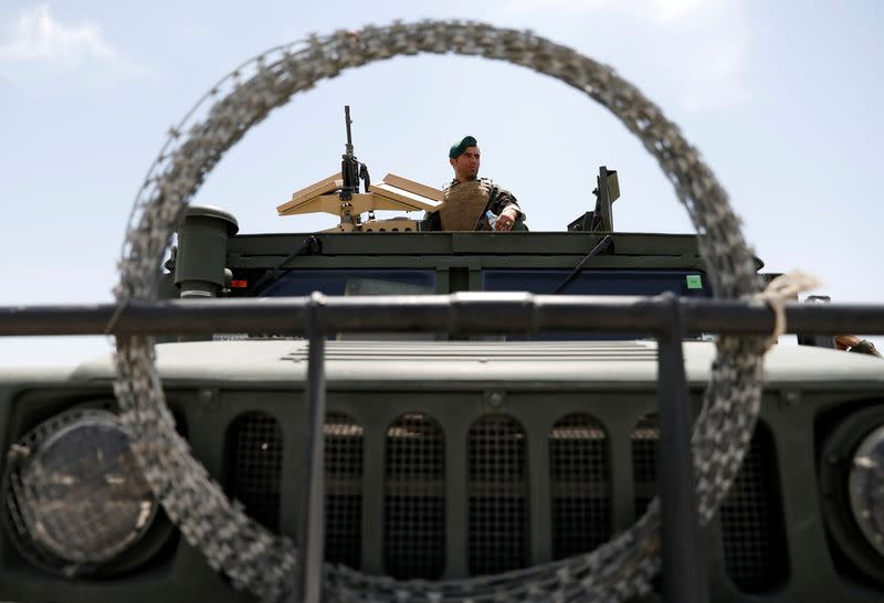 An Afghan security forces member keeps watch as he sits in an army vehicle in Bagram U.S. air base, after American troops vacated it, in Parwan province