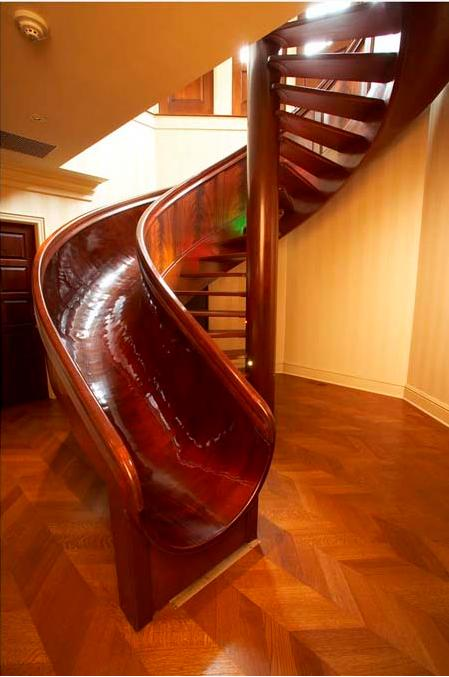 """My 28-foot wooden circular mahogany slide took more than 15 months to  build. The slide was formed with a cold-molding technique that used two  kinds of mahogany, 30 gallons of epoxy, and 40,000 staples, 36,000 of  which were removed after the epoxy dried. Once the slide was installed  in my home, spiraling stairs were built around it so that they were  ""married"" to its curvature,"" explains inventor Scott A. Jones.<br><br>(Photo courtesy of <a target=""_blank"" href=""http://www.scottajones.com"">Scott A. Jones</a>)"