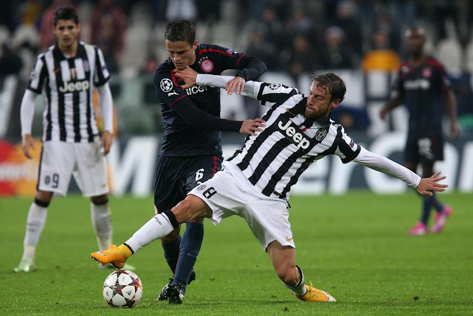 Juventus' midfielder Claudio Marchisio (R) fights for the ball with Olympiakos' Dutch midfielder Ibrahim Afellay during their Champions League Group A football match in Turin on November 4, 2014 (AFP Photo/Marco Bertorello)