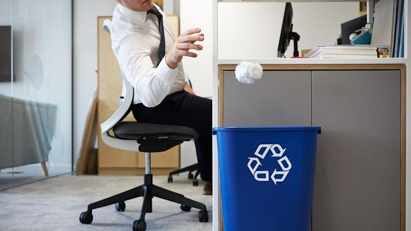 Man at desk throwing screwed up paper into recycling bin.