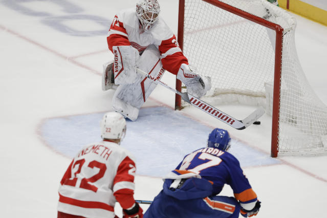 Detroit Red Wings goaltender Calvin Pickard, above, reaches for the puck shot by New York Islanders' Leo Komarov, right, for a goal during the third period of an NHL hockey game Tuesday, Jan. 14, 2020, in Uniondale, N.Y. The Islanders won 8-2. (AP Photo/Frank Franklin II)