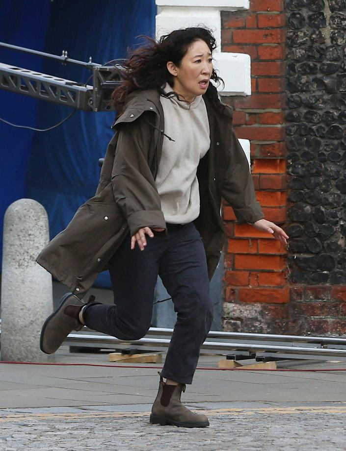<p>Sanda Oh sprints down the street while filming a scene for Killing Eve on Sept. 8 in Kent, England. </p>