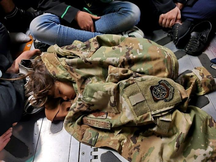 An Afghan child sleeps on the cargo floor of a U.S. Air Force C-17 Globemaster III, kept warm by the uniform of the C-17 loadmaster, during an evacuation flight from Kabul, Afghanistan, Aug. 15, 2021