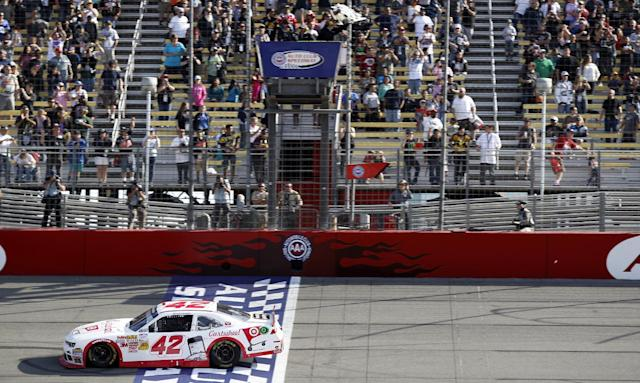 Kyle Larson (42) crosses the finish line to win the NASCAR Nationwide Series auto race in Fontana, Calif., Saturday, March 22, 2014. (AP Photo/Alex Gallardo)