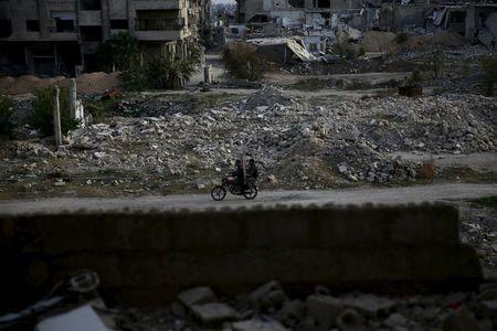Men ride a motorbike near damaged buildings in the rebel-controlled area of Jobar, a suburb of Damascus