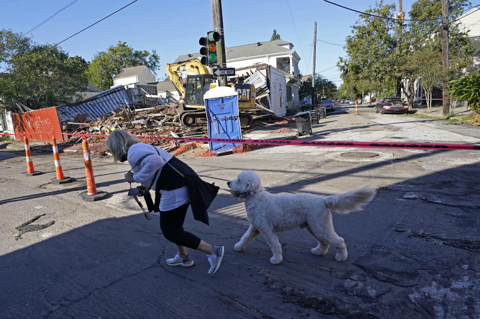 A person and dog walk past an unoccupied structure that collapsed the previous day as Hurricane Zeta swept through New Orleans, Thursday, Oct. 29, 2020. The storm left much of the city and metro area without power. (AP Photo/Gerald Herbert)