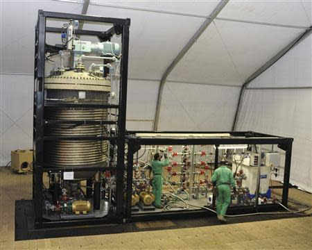A handout photo released by the U.S. Army Edgewood Chemical Biological Center (ECBC) to Reuters on October 10, 2013 shows specialized technicians from ECBC's Chemical Biological Application and Risk Reduction (CBARR) Business Unit work on the Field Deployable Hydrolysis System (FDHS), a new Department of Defense (DoD) elimination technology designed to neutralize bulk amount of known chemical warfare agents and their precursors. REUTERS/The U.S. Army Edgewood Chemical Biological Center/Handout