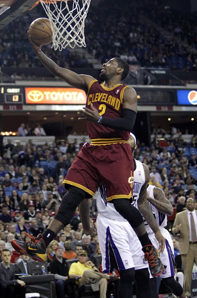 Cleveland Cavaliers guard Kyrie Irving, left, goes to the basket against Sacramento Kings center DeMarcus Cousins during the first quarter of an NBA basketball game in Sacramento, Calif., Sunday, Jan. 12, 2014. (AP Photo/Rich Pedroncelli)