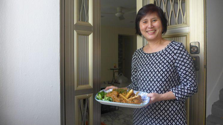 Home cook Josephine Goh carrying a plate of chicken rendang at her doorstep. (Yahoo Lifestyle Singapore)