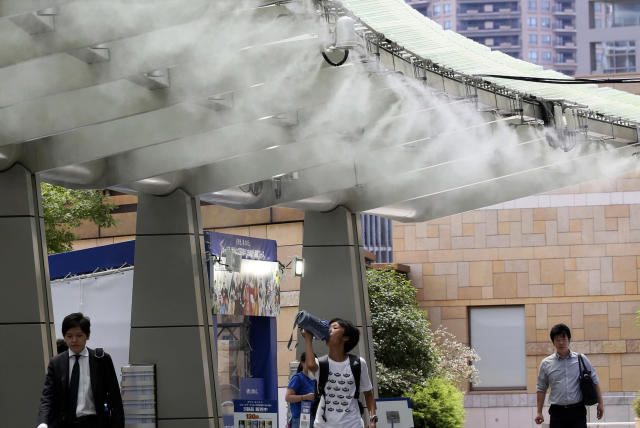 <p>People cool down under the cooling mist spot in Tokyo, Monday, July 13, 2018. (Photo: Koji Sasahara/AP) </p>