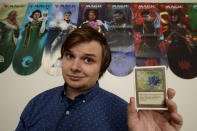 Austin Deceder, displays a Black Lotus Magic card in his home office Friday, Aug. 27, 2021, in Kansas City, Mo. Prices of the collectable cards and vintage video games that Deceder and others buy and sell have skyrocketed in the past few months to the dismay of hobbyists. (AP Photo/Charlie Riedel)