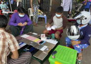 People wearing face masks check used mobile phones at a second-hand market in Yangon, Myanmar, Thursday, July 8, 2021. Myanmar is facing a a rapid rise in COVID-19 patients and a shortage of oxygen supplies just as the country is consumed by a bitter and violent political struggle since the military seized power in February. (AP Photo)