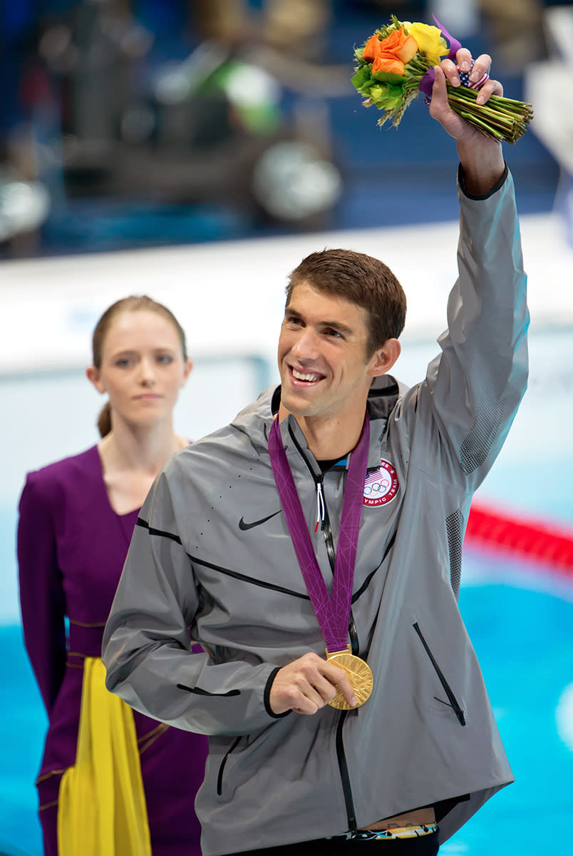 <p>Michael Phelps smiles with his gold medal after the medal ceremony in the 100m butterfly on August 3, 2012. The medal was Phelps' 17th career gold medal. (David Eulitt/Kansas City Star/MCT via Getty Images)</p>