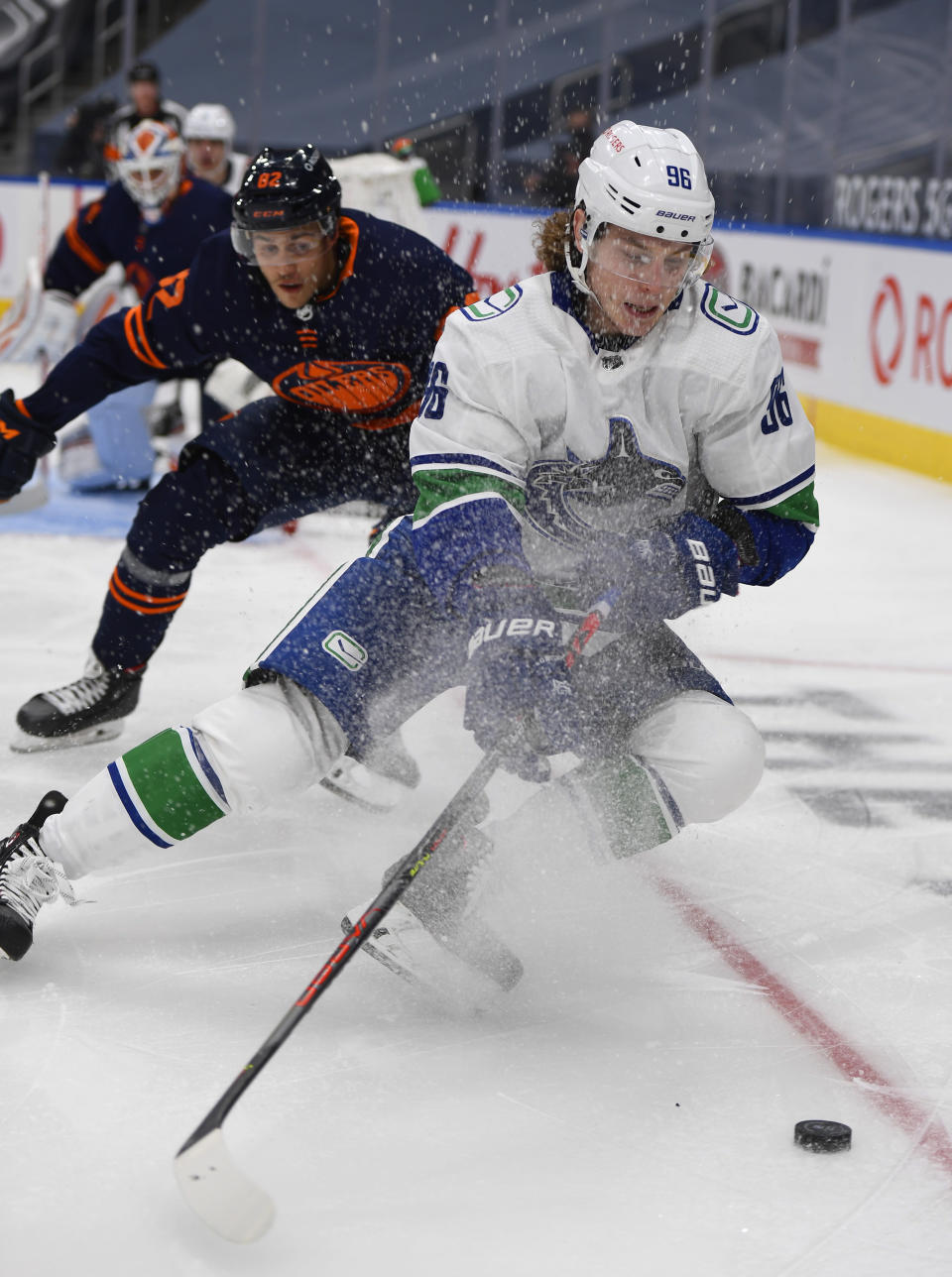 Edmonton Oilers' Caleb Jones (82) chases Vancouver Canucks' Adam Gaudette (96) during the third period of an NHL hockey game Wednesday, Jan. 13, 2021, in Edmonton, Alberta. (Dale MacMillan/The Canadian Press via AP)