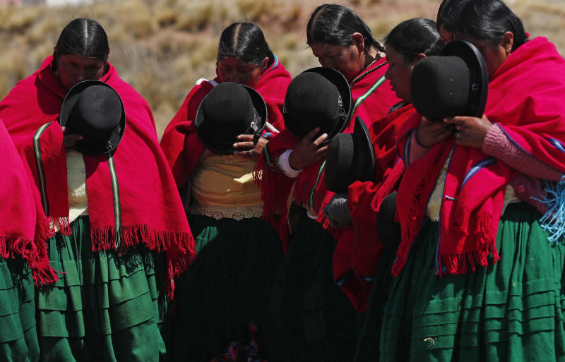 Aymara women pray before the day's start of an excavation of pre-Hispanic vessels at the Kalasasaya temple in the ancient city of Tiwanaku, Bolivia, Wednesday, Sept. 18, 2019. Bolivian archaeologists are presenting the findings of a recent discovery of ancient vessels unearthed in a dig on the site once home to one of the most significant pre-Hispanic empires, the Tiwanacota. (AP Photo/Juan Karita)