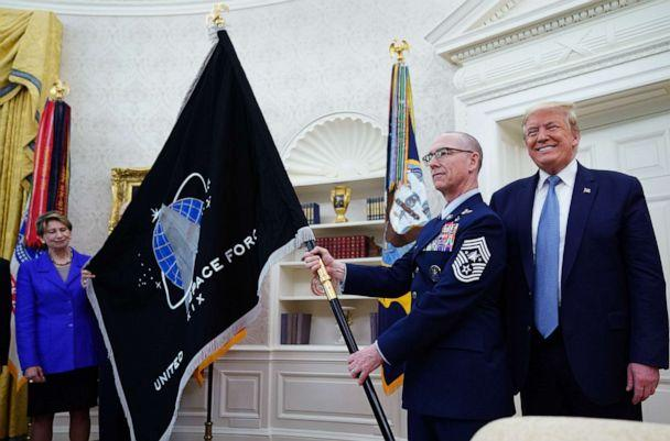 PHOTO: Space Force Senior Enlisted Advisor CMSgt Roger Towberman with President Donald Trump, presents the U.S. Space Force Flag on May 15, 2020, in the Oval Office. (Mandel Ngan/AFP via Getty Images)