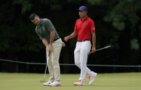 Rory McIlroy of Ireland, left, studies his putt beside Collin Morikawa of United States on the third green during the second round of the men's golf event at the 2020 Summer Olympics on Friday, July 30, 2021, at the Kasumigaseki Country Club in Kawagoe, Japan. (AP Photo/Matt York)