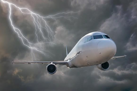 A jetliner flies toward the viewer through dark clouds and a lightning strike.