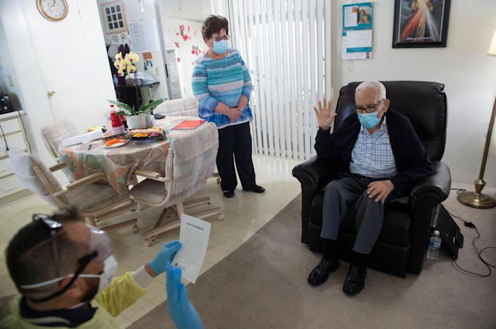 In a rare at-home naturalization ceremony, Felix Taborda Romero, 88, is sworn in as a U.S. citizen by Eugenio Rosado, a supervisory immigration services officer, as his wife, Laura Apitz de Taborda, watches on Monday.