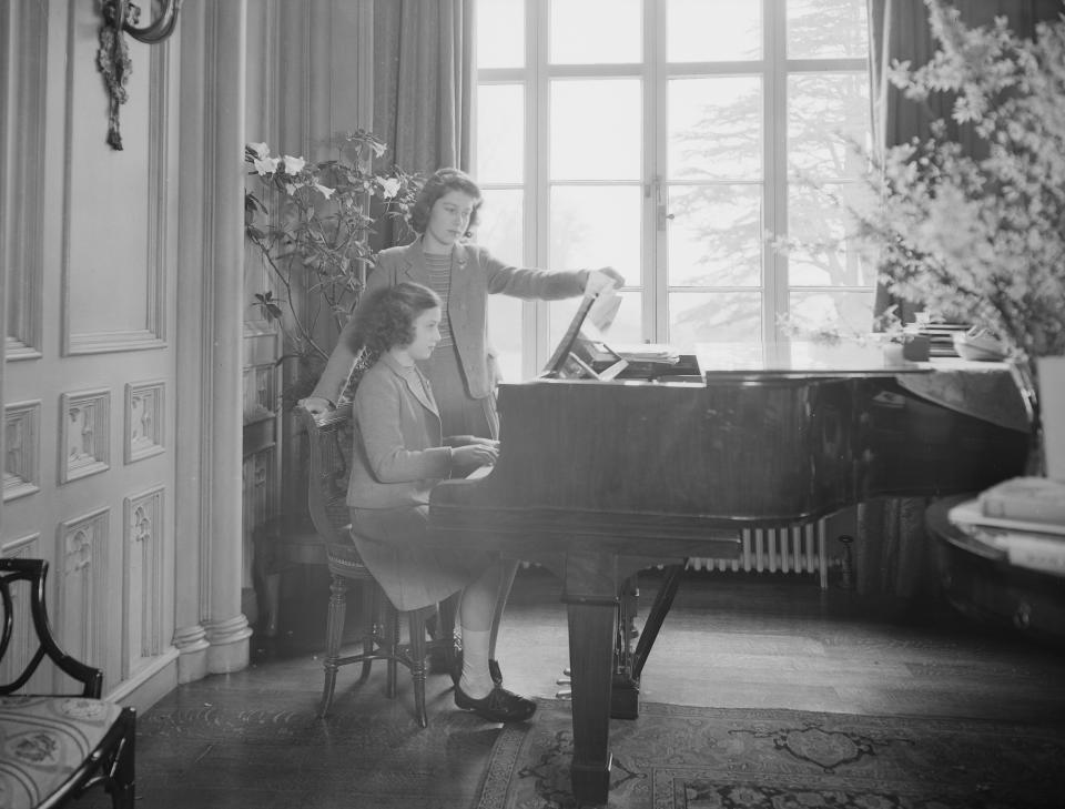 Princess Elizabeth looks on as Princess Margaret plays the piano at the Royal Lodge in Windsor Castle, England on April 11, 1942.  (Photo by Studio Lisa/Getty Images)