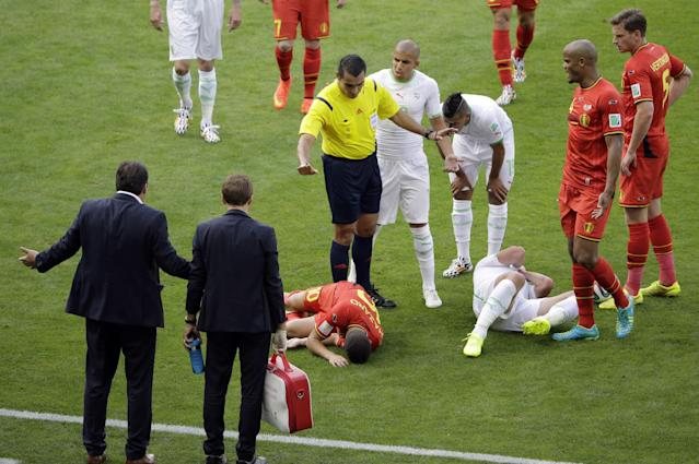 Referee Marco Rodriguez from Mexico gestures as head coach Marc Wilmots, left, protests after Belgium's Eden Hazard, center, collided with Algeria's Mehdi Mostefa, third from right, during the group H World Cup soccer match between Belgium and Algeria at the Mineirao Stadium in Belo Horizonte, Brazil, Tuesday, June 17, 2014. At right is Belgium's Jan Vertonghen, second from right is Belgium's Vincent Kompany. Center is Algeria's Sofiane Feghouli. (AP Photo/Sergei Grits)