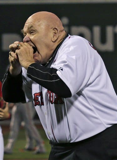 "Former professional wrestler George ""The Animal"" Steele bites the baseball before throwing out the ceremonial first pitch prior to a baseball game against the Baltimore Orioles at Fenway Park in Boston, Friday, Sept. 21, 2012. (AP Photo/Charles Krupa)"