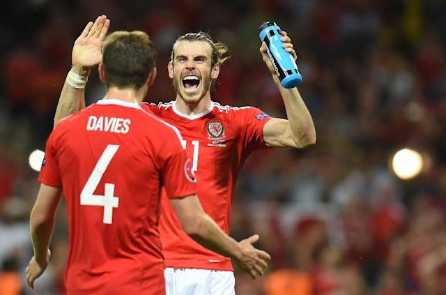 Wales' Gareth Bale celebrates with teammate Ben Davies after their 3-0 win over Russia in their Euro 2016 Group B match at the Stadium Municipal in Toulouse on June 20, 2016 (AFP Photo/Remy Gabalda)