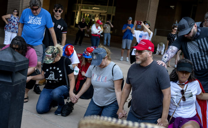 Supporters pray before Republican Reps. Marjorie Taylor Greene and Matt Gaetz held a protest outside City Hall on Saturday, July, 17, 2021, in Riverside, Calif. (Cindy Yamanaka/The Orange County Register via AP)