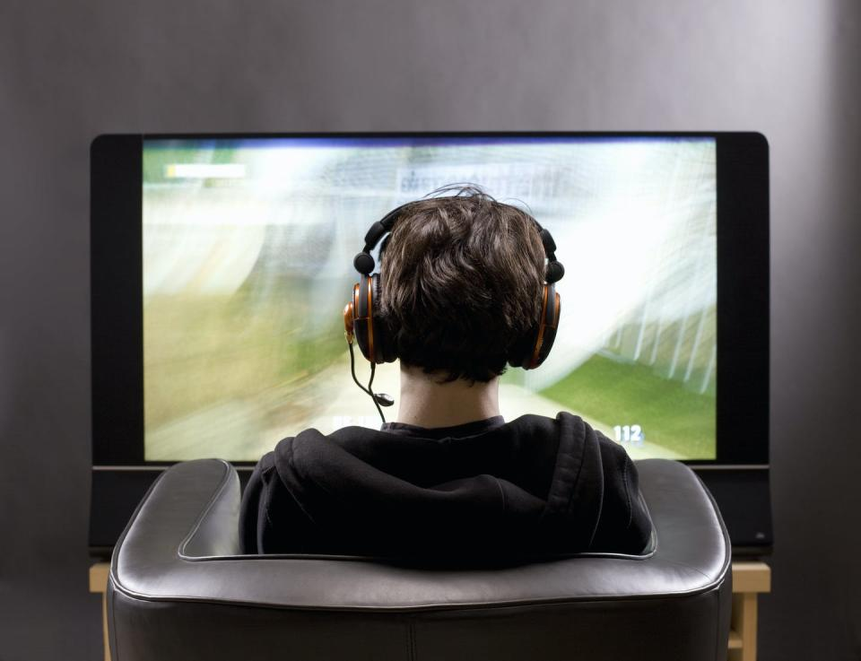 Teenage boy sits in chair playing a video game on a big flat screen.