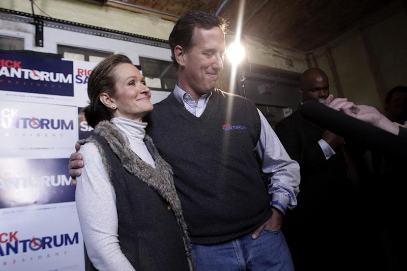 """FILE - In this March 30, 2012 file photo, then-Republican presidential candidate, former Pennsylvania Sen. Rick Santorum is joined by his wife Karen as he talks to reporters in Chippewa Falls, Wis. The Republican primary campaign is already fading into memory. Remember Herman Cain's 9-9-9 tax plan? Newt Gingrich's """"moon base"""" proposal? Or Rick Perry's """"oops"""" moment _ when he couldn't recall that third federal agency he wanted to eliminate? (AP Photo/Jae C. Hong, File)"""