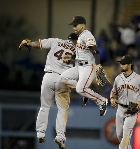 San Francisco Giants' Andres Torres, right, and Pablo Sandoval celebrate their team's 3-0 win against the Los Angeles Dodgers after a baseball game in Los Angeles, Tuesday, April 2, 2013. (AP Photo/Jae C. Hong)