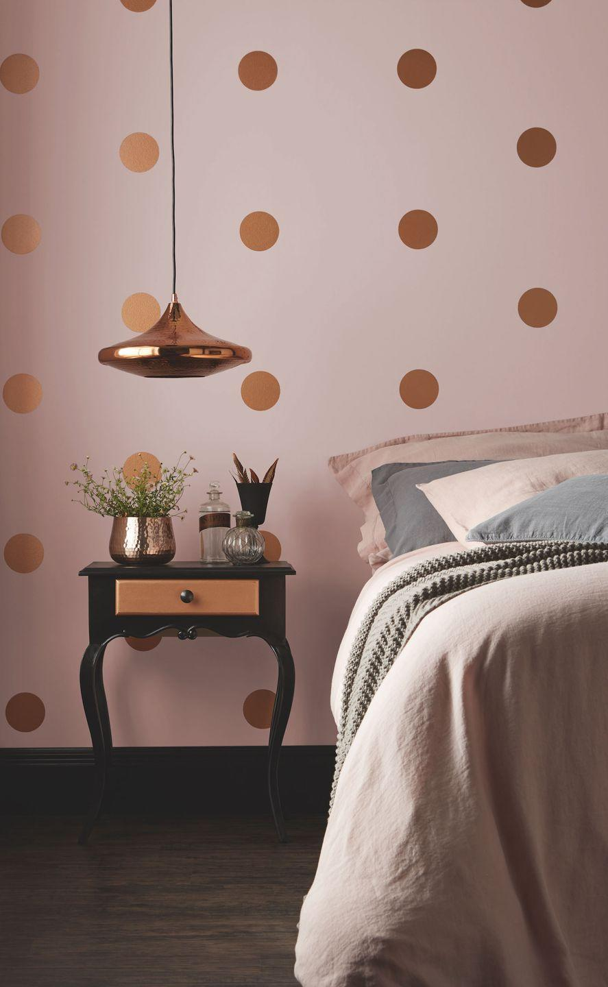 """<p>Using paint as a decorative element is a really fun way to make walls look individual. For this girls' bedroom idea, use a circle template to make the gold dots after you've painted the wall pink. And don't forget you can paint furniture too – this elegant side table is painted black with a gold drawer to match the walls. Then add in a gold pendant and some dusky pink bedding to accessorise.</p><p>Pictured: Pashmina, Copper and Jet Black emulsion, <a href=""""https://www.crownpaints.co.uk/products/standard-emulsion/matt/pashmina%C2%AE/182"""" rel=""""nofollow noopener"""" target=""""_blank"""" data-ylk=""""slk:Crown"""" class=""""link rapid-noclick-resp"""">Crown</a></p>"""