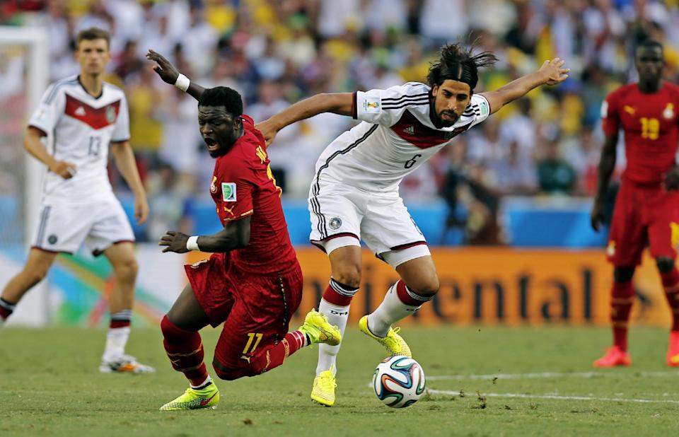 Ghana's Sulley Muntari, left, is challenged by Germany's Sami Khedira during the group G World Cup soccer match between Germany and Ghana at the Arena Castelao in Fortaleza, Brazil, Saturday, June 21, 2014. (AP Photo/Frank Augstein)