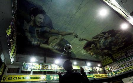 A boy plays soccer as images of Lionel Messi and Diego Maradona are seen depicted on the ceiling in a recreation of Michelangelo's Sistine Chapel painting, by Argentine artist Santiago Barbeito, at Sportivo Pereyra club in Buenos Aires, Argentina April 26, 2018. REUTERS/Marcos Brindicci