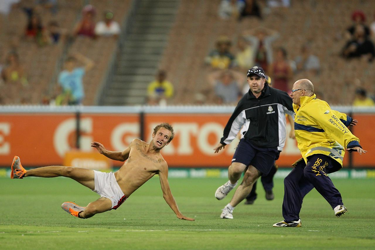 MELBOURNE, AUSTRALIA - JANUARY 11:  A pitch invader tries to outrun security during game one of the Commonwealth Bank One Day International series between Australia and Sri Lanka at Melbourne Cricket Ground on January 11, 2013 in Melbourne, Australia.  (Photo by Robert Prezioso/Getty Images)