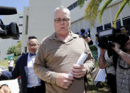 FILE - In this June 6, 2019, file photo, Scot Peterson, center, leaves the Broward County Jail after posting bail in Fort Lauderdale, Fla. The school security officer on duty the day of the 2018 mass shooting at Florida's Marjory Stoneman Douglas High School faces 11 charges, including child neglect and negligence, for not entering the building to confront the gunman. Peterson has pleaded not guilty and awaits trial. (AP Photo/Lynne Sladky, File)