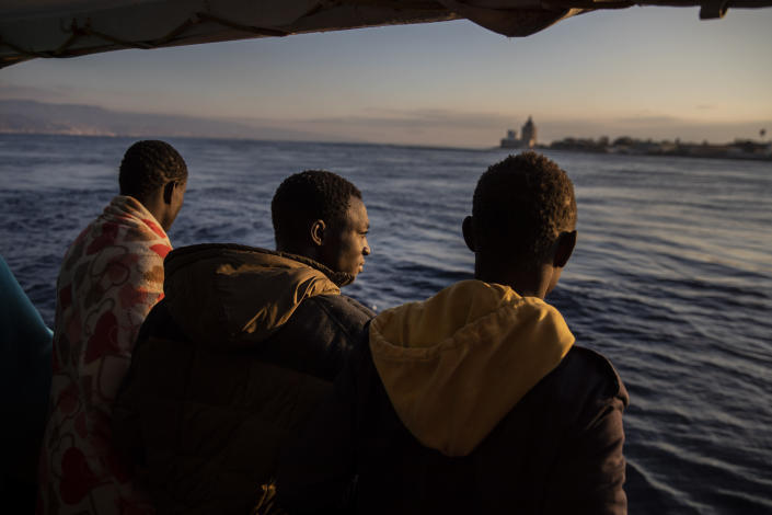 Men who were rescued off the Libyan coast on Friday, watch the city of Messina from the deck of the Open Arms rescue vessel as the ship enters the port located on the island of Sicily, Italy, Wednesday, Jan. 15, 2020. (AP Photo/Santi Palacios)