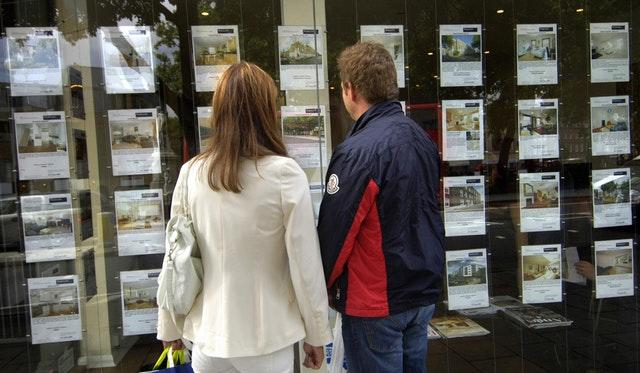 A couple look at homes in an estate agent's window