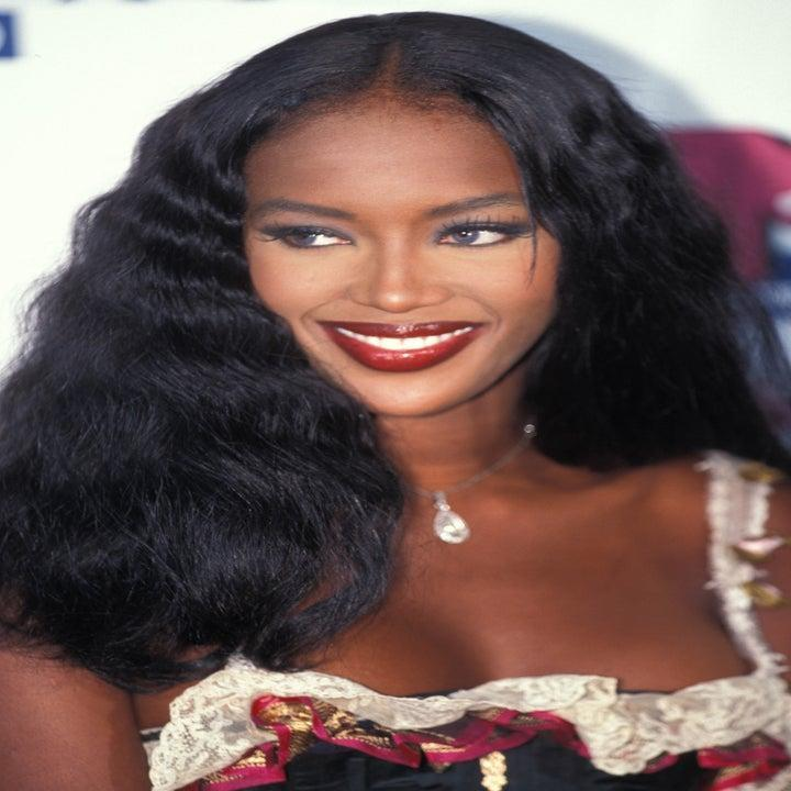 Photo of Naomi Campbell in deep red lipstick and a tank top