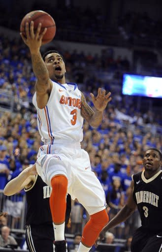 Florida's Mike Rosario (3) goes for the basket as Vanderbilt's Festus Ezeli (3) watches during the first half of an NCAA college basketball game in Gainesville, Fla., Saturday, Feb. 4, 2012. (AP Photo/Phil Sandlin)