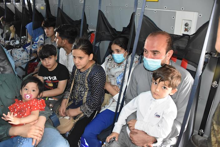 A family sits on a Turkish Armed Forces aircraft during evacuation in Kabul. (Aykut Karadag/Anadolu Agency via Getty Images)