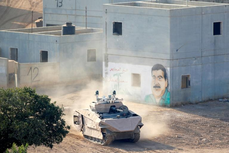 An Israeli tank drives through a mock Arab village used for battle training, at a base in northern Israel (AFP Photo/JACK GUEZ)