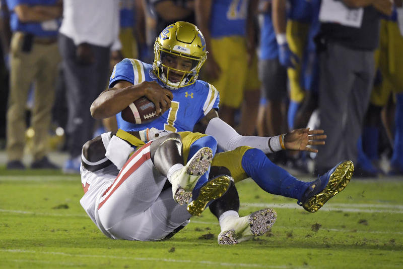 UCLA quarterback Dorian Thompson-Robinson, top, is sacked by Oklahoma linebacker Brian Asamoah during the second half of an NCAA college football game Saturday, Sept. 14, 2019, in Pasadena, Calif. (AP Photo/Mark J. Terrill)