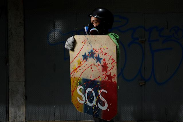 "<p>A demonstrator holding a rudimentary shield poses for a picture before a rally against Venezuelan President Nicolas Maduro's government in Caracas, Venezuela, May 27, 2017. He said: ""I protest for freedom. I'm 18 and I'm not to be blamed for this, I never voted for Chavez or Maduro. I want to know that I can study and that I can aspire to something better. This regime has robbed us of everything, robbed us of the quality of life and opportunities, so that we have nothing more to do than be here to defend our rights."" (Photo: Carlos Garcia Rawlins/Reuters) </p>"