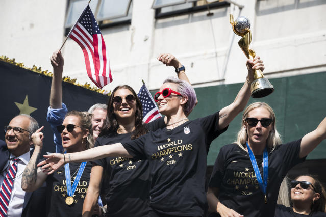 Megan Rapinoe #15 of United States holds the 2019 FIFA World Cup Champion Trophy, Ashlyn Harris #18 of United States Alex Morgan #13 of United States and Allie Long #20 of United States ride on the World Champions float as it rides down Broadway for the Ticker Tape through the Canyon of Heroes. This celebration was put on by the City of Manhattan to honor the team winning the 2019 FIFA World Cup Championship title, their fourth, played in France against Netherlands, at the City Hall Ceremony in the Manhattan borough of New York on July 10, 2019, USA. (Photo by Ira L. Black/Corbis via Getty Images)