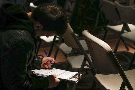 A man fills out paperwork before a screening session for seasonal jobs at Coney Island in the Brooklyn borough of New York
